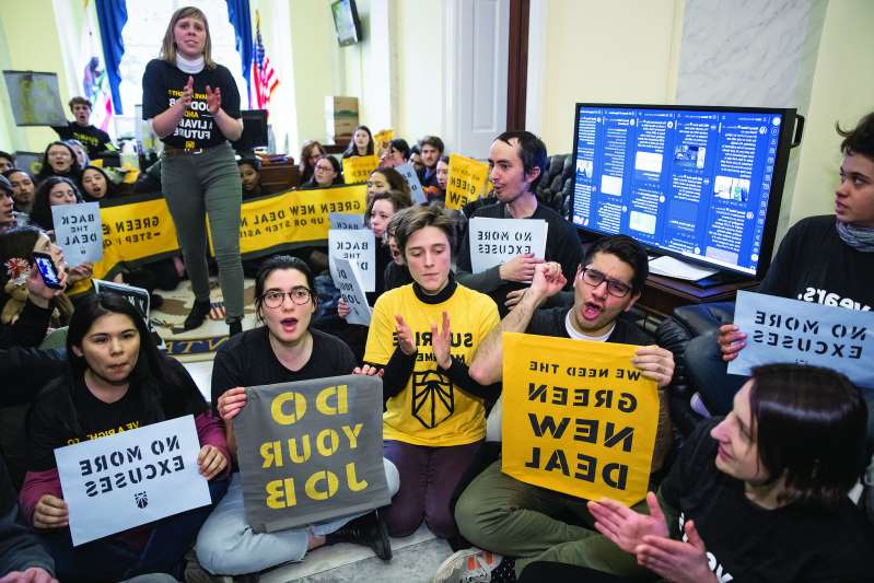 a group of people holding a sign posing for the camera: Sunrise Movement activists occupy the office of House Democratic Leader Nancy Pelosi of California, the speaker-designate for the new Congress, in 2018. (AP Photo/J. Scott Applewhite)