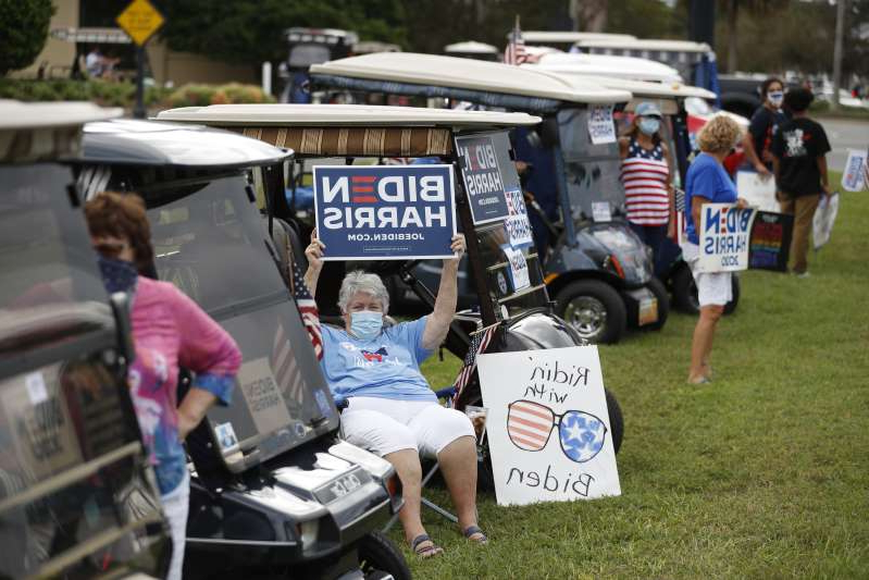 a group of people riding on the back of a truck: Supporters of Democratic Presidential nominee Joe Biden rally during President Donald Trump's campaign stop at The Villages Polo Club on October 23, 2020 in The Villages, Florida. Supporters gather to help increase voter turn out in a heavily Republican voter district.