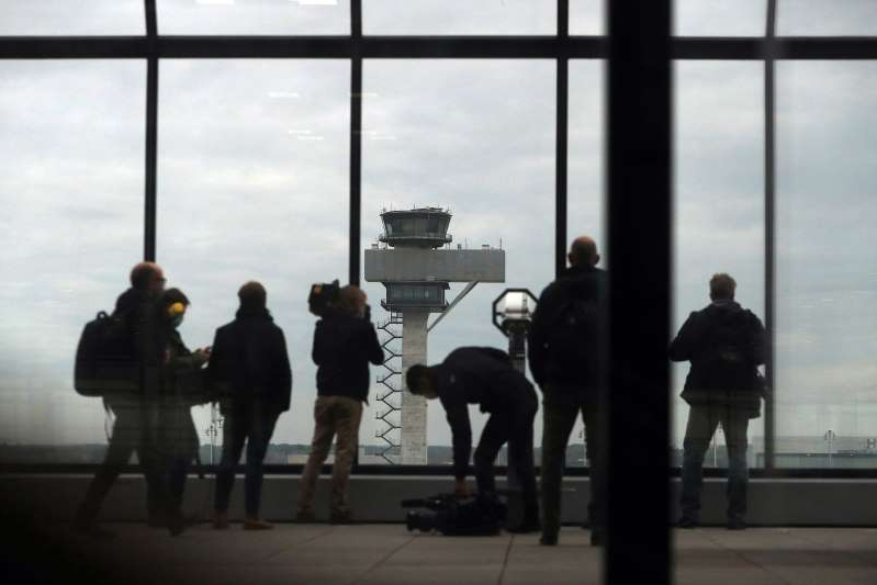 a group of people standing next to a window: Berlin Brandenburg Airport Ahead of Long Delayed Opening