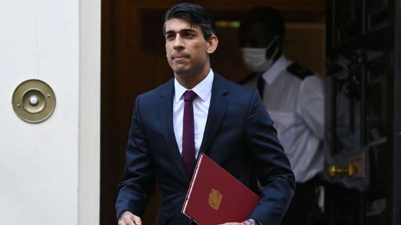 a man wearing a suit and tie: Chancellor Rishi Sunak had a chart in his office comparing the UK's furlough scheme with European equivalents