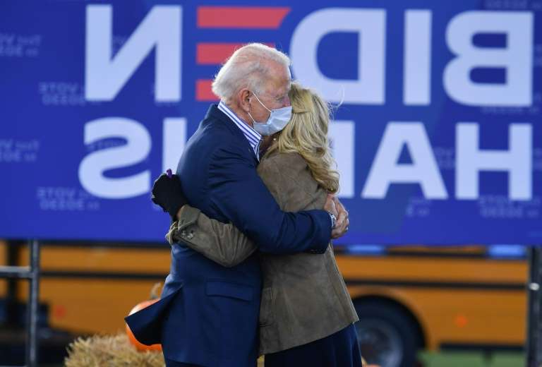 a person holding a sign: Joe and Jill Biden have been a Washington power couple for more than 40 years