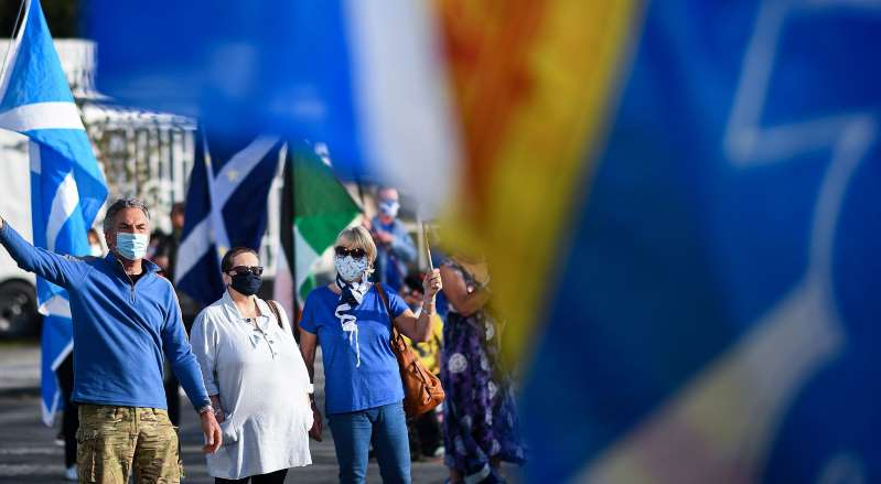 a person standing on a stage: GLASGOW, SCOTLAND - SEPTEMBER 17: Members of the pro-indy group All Under One Banner hold a rally for independence outside BBC Scotland on September 17, 2020 in Glasgow, Scotland. The group has stated