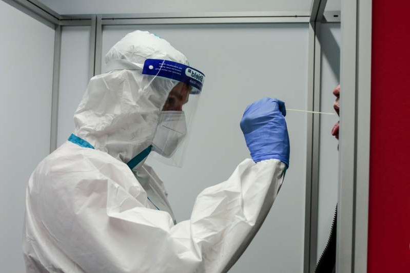 a person wearing a mask: A health worker wearing personal protective equipment (PPE) administers a swab test on a traveler at a Covid-19 test center, operated by Centogene NV, at Duesseldorf Airport in Duesseldorf, Germany, on Wednesday, Sept. 30, 2020. Germany may join other European nations in limiting the number of people at private and public gatherings in areas with high coronavirus infection rates, as officials across the continent labor to reverse a recent uptick in cases.