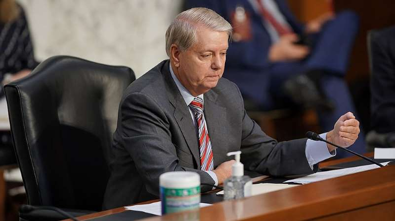 Lindsey Graham in a suit sitting at a table: GOP faces fundraising reckoning as Democrats rake in cash