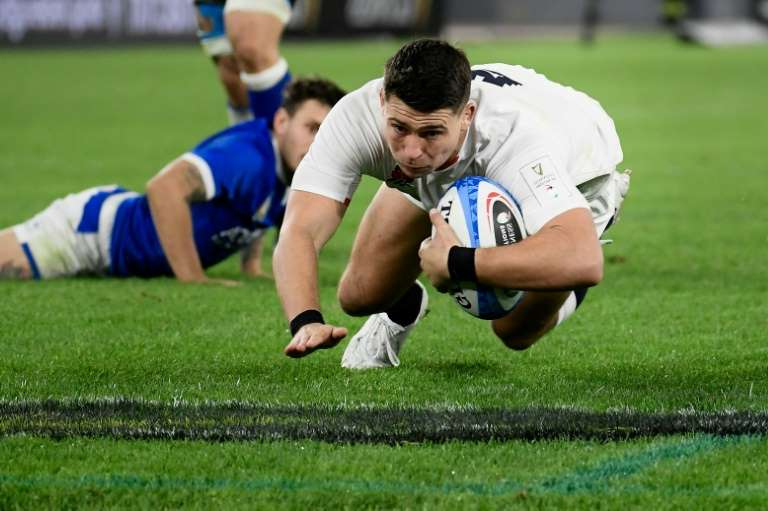 a man holding a football ball on a field: England's scrum-half Ben Youngs marked his 100th cap with two tries.