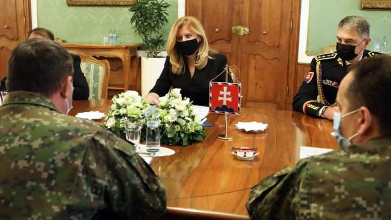 a man sitting at a table: President Caputova (C) consulted army chiefs about the mass testing plans on Friday