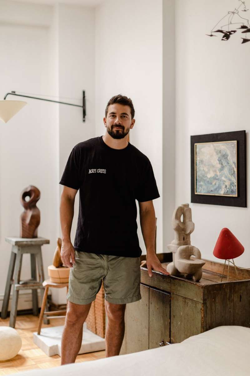 "a man standing in a room: ""I kind of like being a jack-of-all-trades, being able to move throughout the design world organically,"" says Jonny Ribeiro, a designer, collector, and dealer. He's pictured here in his Brooklyn apartment, with a 1960s metal lamp, a 1970s stone sculpture by Bernice Dritz-Epstein, and an impressionist seascape by Uta Von Bern."