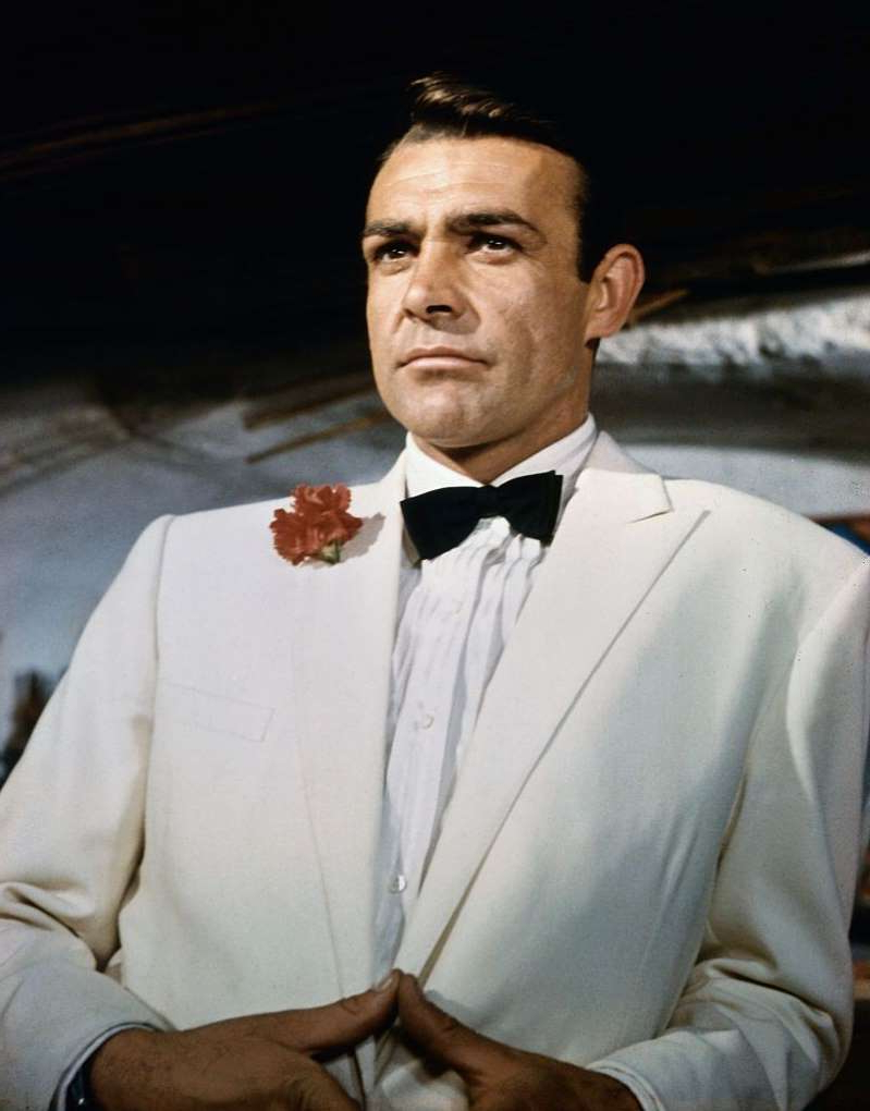 a man wearing a suit and tie: Sean Connery as James Bond in the movie Goldfinger.