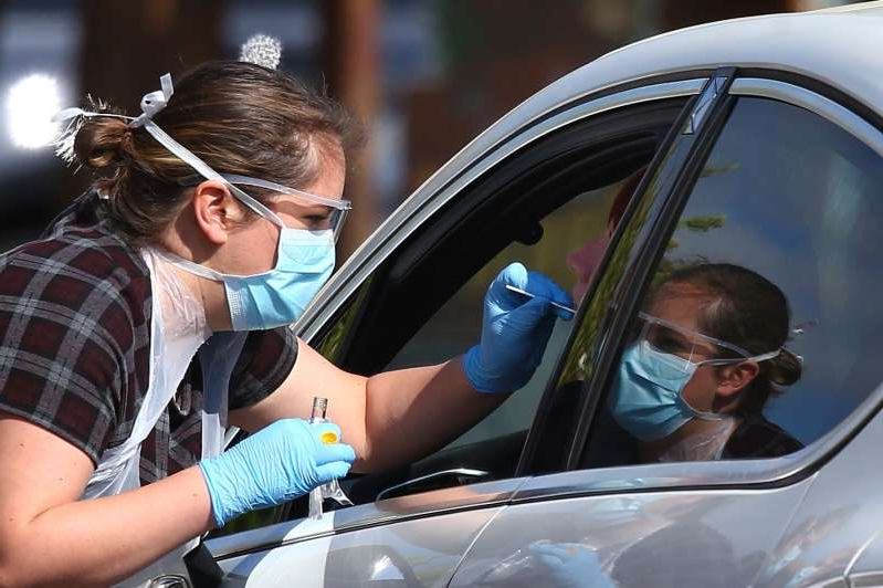 a woman wearing sunglasses driving a car: CHESSINGTON, ENGLAND - APRIL 25: A medical worker takes a swab at a drive-in COVID-19 testing centre at Chessington World of Adventures Resort theme park on April 24, 2020 in Chessington, United Kingdom. The British government has extended the lockdown restrictions first introduced on March 23 that are meant to slow the spread of Coronavirus (COVID-19). (Photo by Hollie Adams/Getty Images)