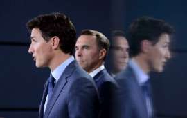 Bill Morneau wearing a suit and tie: Prime Minister Justin Trudeau makes an announcement with Bill Morneau, then the finance minister, in Ottawa on Tuesday, June 18, 2019.