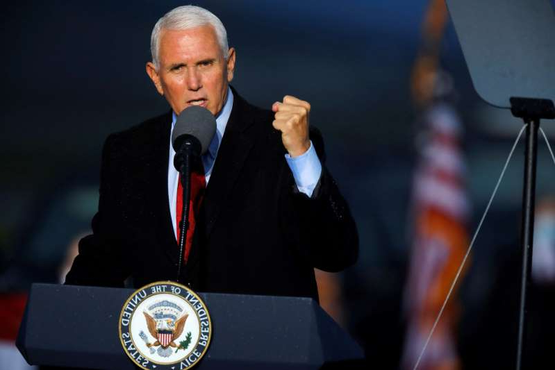 Mike Pence wearing a suit and tie talking on a cell phone: FILE PHOTO: U.S. Vice President Mike Pence rally in Kinston, North Carolina