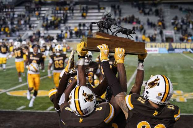 Slide 1 of 14: The Wyoming Cowboys celebrate with the Paniolo Trophy after beating Hawaii at Jonah Field at War Memorial Stadium.