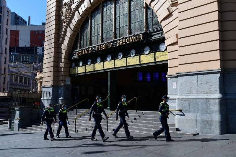 Police officers are seen outside Flinders Street Station in Melbourne