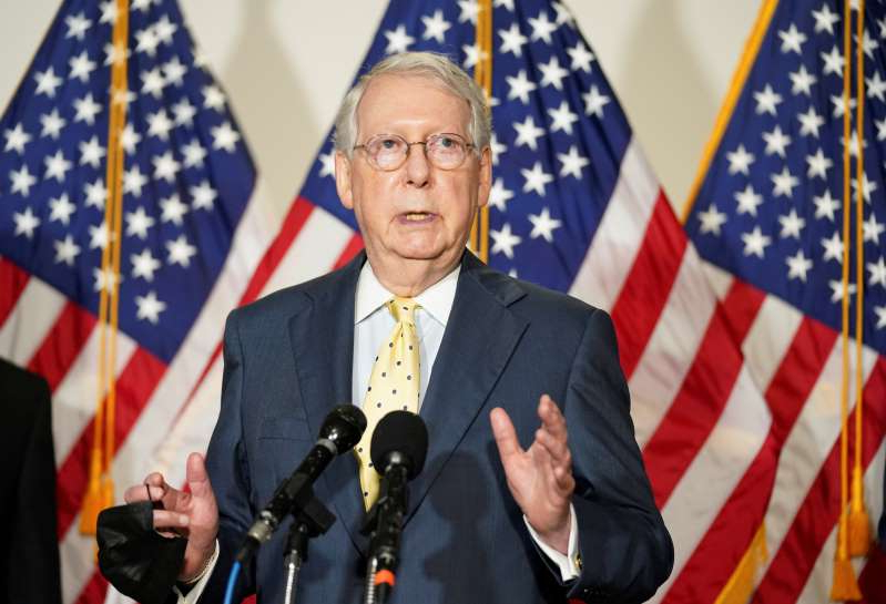 Mitch McConnell wearing a suit and tie standing in front of a flag