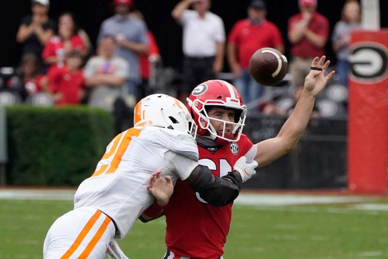 a baseball player holding a bat on a field: Georgia quarterback Stetson Bennett (13) is hit by Tennessee linebacker Morven Joseph (19) as he releases a pass in the first half of an NCAA college football game Saturday, Oct. 10, 2020, in Athens, Ga. (AP Photo/John Bazemore)