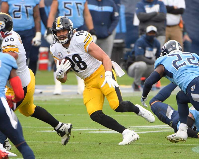a group of football players playing a football game: Pittsburgh Steelers tight end Vance McDonald (89) runs the ball against the Tennessee Titans during the first half at Nissan Stadium.