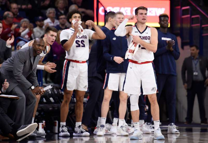 a group of people standing in front of a crowd: Gonzaga players react from the bench after a basket during their 2020 game against Pepperdine at McCarthey Athletic Center.