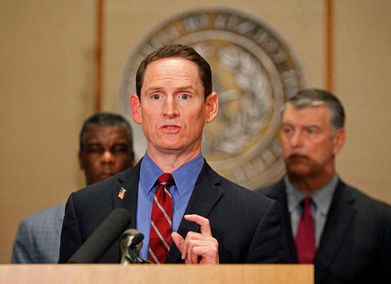 Aaron Smith wearing a suit and tie: Dallas County Judge Clay Jenkins, flanked by (L-R) Dallas Mayor Mike Rawlings and Dallas County Health and Human Services Director Zachary Thompson, answers questions at a press conference concerning the second health care worker to contract Ebola, at the Dallas County Commissioners Court on October 15, 2014 in Dallas, Texas. Jenkins has asked Governor Greg Abbott to consider more COVID-19 restrictions for North Texas.