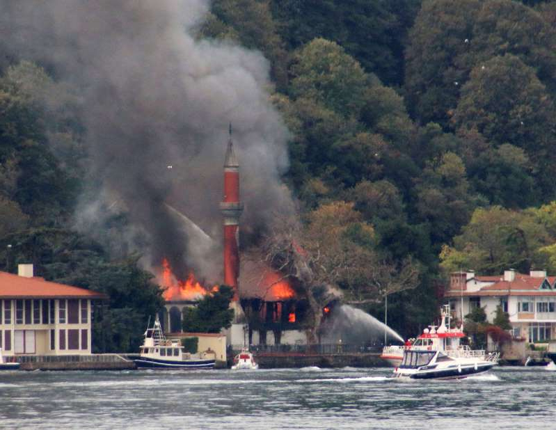 A fire engulfs Vanikoy Mosque, a historic wooden mosque, in Istanbul, Sunday, Nov. 15, 2020. The Vanikoy Mosque, built in the 17th century during the reign of Ottoman Sultan IV Mehmed, is located on the Asian side of Istanbul along the Bosporus Strait. Turkish firefighters were trying to put out the blaze from both land and sea. (DHA via AP)