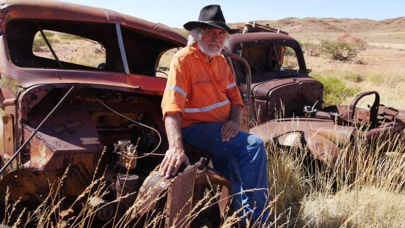 a man riding on the back of a truck: Marshall Smith and what's left of the cars that carried workers in the landmark 1946 Pilbara strike. (ABC Rural: James Liveris)