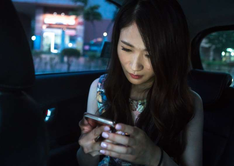 a woman holding a cell phone: South korean woman called juyeon reading text messages on her mobile phone, national capital area, seoul, South Korea on May 31, 2016 in Seoul, South Korea.