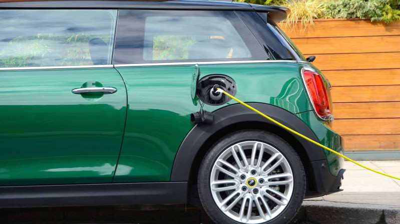 a green car parked on the side of a building: Green Mini Electric plugged into an electric car charger