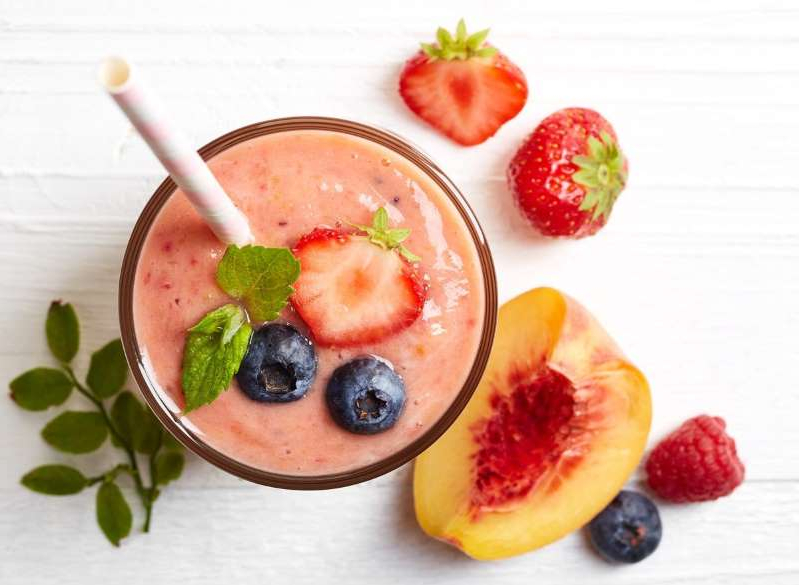 a bowl of fruit on a plate: fruit smoothie blueberries strawberries peaches