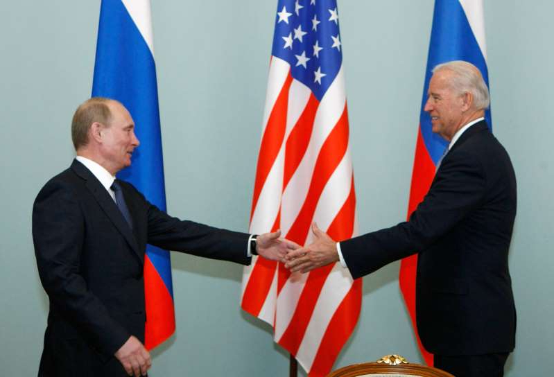 Joe Biden standing in front of a flag: Then-Vice President Joe Biden shakes hands with Russian Prime Minister Vladimir Putin in Moscow, Russia on March 10, 2011.