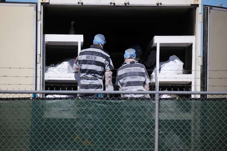 a close up of a truck: Low-level inmates from El Paso County detention facility work loading bodies wrapped in plastic into a refrigerated temporary morgue trailer in a parking lot of the El Paso County Medical Examiner's office on November 16, 2020 in El Paso, Texas. The inmates, who are also known as trustees, are volunteering for the work and earn $2 per hour amid a surge of COVID-19 cases in El Paso. Texas surpassed 20,000 confirmed coronavirus deaths today, the second-highest in the U.S., with active cases in El Paso now well over 30,000.