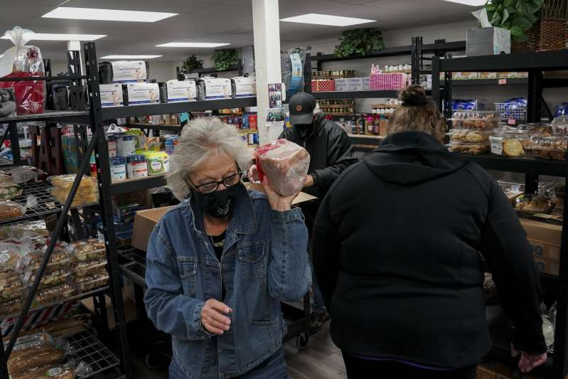 a man and a woman standing in front of a store: Sharon Ames, executive director of the Fauquier Community Food Bank, and others prepare food to be distributed Nov. 17 in Warrenton, Va. The food bank is struggling to source Thanksgiving turkeys.