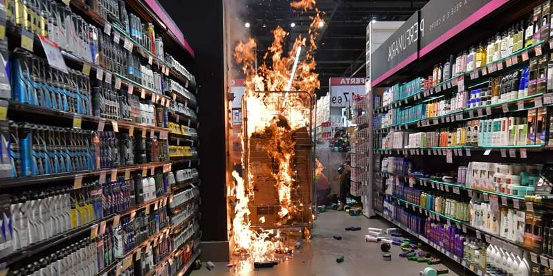 a group of people in a store: Products burn at a supermarket Carrefour in Sao Paulo, Brazil, on November 20, 2020 on Black Consciousness Day after protesters invaded the place during a protest against racism and the death on the eve of a black man who was beaten by white security agents in a supermarket of the same chain in Porto Alegre and who later died. NELSON ALMEIDA/AFP via Getty Images