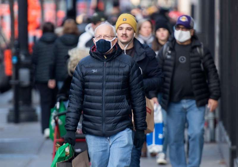 a group of people walking down the street: People wear face masks as they walk along a street in Montreal, Saturday, Nov. 21, 2020, as the COVID-19 pandemic continues in Canada and around the world.THE CANADIAN PRESS/Graham Hughes