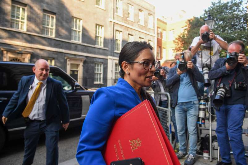 a group of people walking down the street: Priti Patel, U.K. home secretary, arrives for a meeting of cabinet ministers in London, U.K., on Tuesday, Sept. 15, 2020. U.K. Prime Minister Boris Johnson's plan to renege on part of the Brexit divorce deal passed its first hurdle in Parliament late Monday after a bruising debate in which senior members of his own party denounced the move.