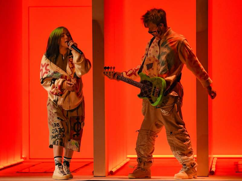 a man standing next to a woman: Finneas O'Connell and Billie Eilish perform at the 2020 AMAs.