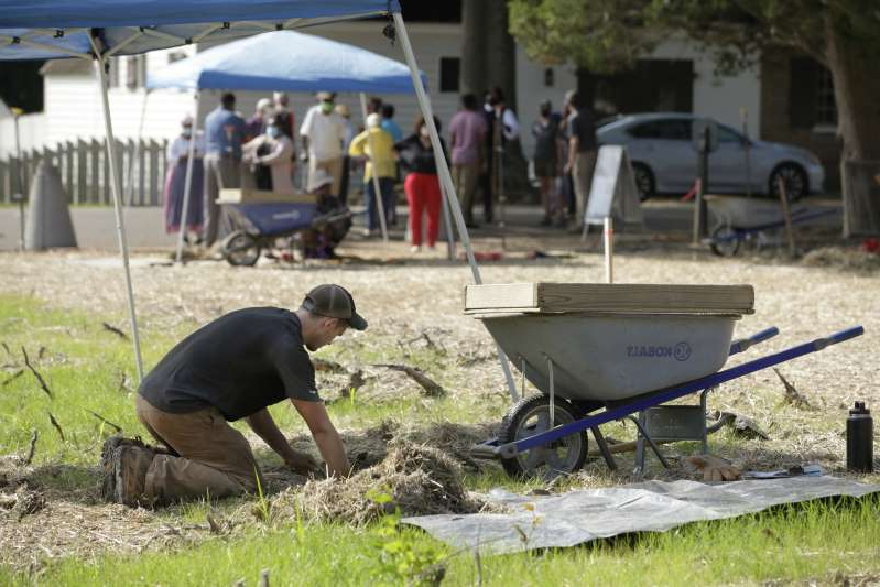 a man that is sitting in the grass: Archaeologist Kyle Brubaker digs in Colonial Williamsburg at the historic site of First Baptist Church, one of the oldest African American churches in the United States.