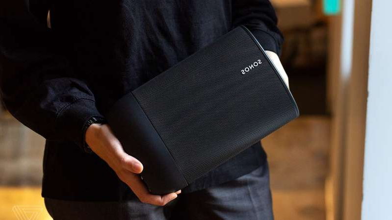 a person holding a suitcase: The Sonos Move wireless speaker