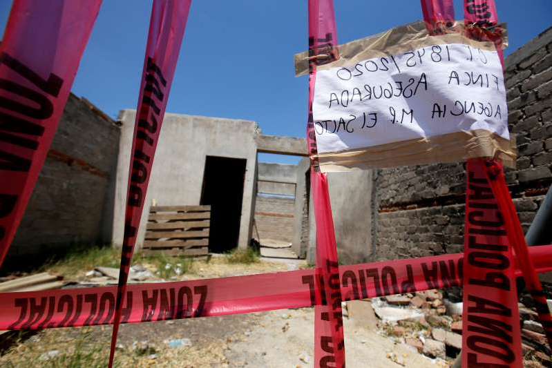 a sign on the side of a building: A taped-off unfinished construction at the farm a clandestine mass grave was discovered in the municipality of El Salto, outside the western Mexican city of Guadalajara, in Jalisco State, taken on May 10, 2020. Another mass grave was found in the region last month.