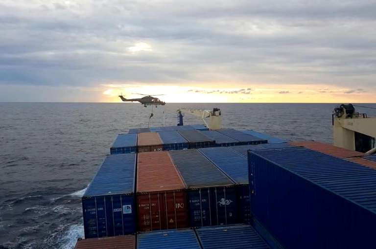 a wooden boat in a body of water: Footage filmed by crew shows a German soldier landing from a helicopter onto the Turkish cargo ship