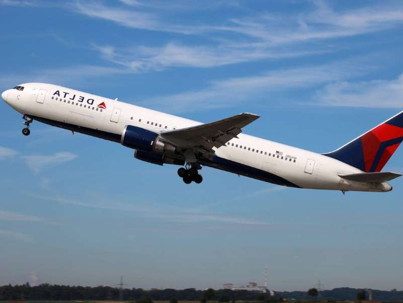 a large passenger jet flying through a blue sky: Delta Air Lines is awarding employees with free travel.