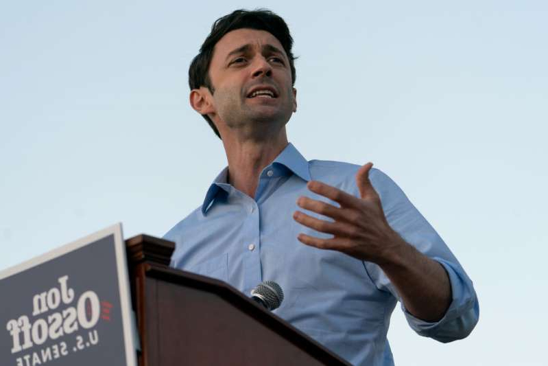 a man holding a sign: Democratic U.S. Senate candidate Jon Ossoff speaks at a campaign event on November 19, 2020 in Jonesboro, Georgia. Democratic U.S. Senate candidates Raphael Warnock and Jon Ossoff are campaigning in the state ahead of their January 5 runoff races against Sen. Kelly Loeffler (R-GA) and Sen. David Perdue (R-GA). Ossoff has highlighted GOP voters who think President Donald Trump's election victory was stolen as he seeks to defeat Perdue.