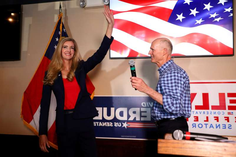 a person holding a sign: Sen. Kelly Loeffler (R-Ga.) salutes as she takes the stage after Sen. Rick Scott (R-Fla.) delivered a speech during a campaign event Nov. 13. (Dustin Chambers/Reuters)