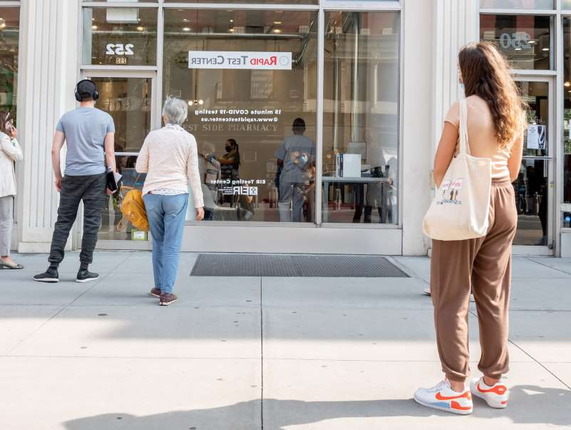 a person standing on a sidewalk: People stand outside a COVID-19 rapid testing centre on the Upper West Side of New York City on September 18, 2020.