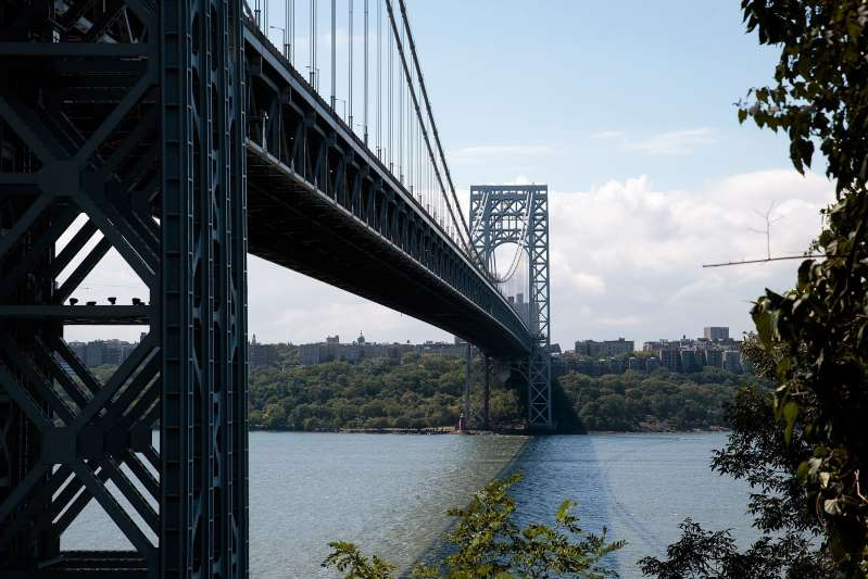 a train crossing a bridge over a body of water: FORT LEE, NJ - SEPTEMBER 7: A view of the George Washington Bridge from Fort Lee Historic Park, September 7, 2016 in Fort Lee, New Jersey. Jury selection begins on Thursday for the New Jersey 'Bridgegate' trial. Two former allies of New Jersey Governor Chris Christie stand accused of intentionally causing traffic gridlock in Fort Lee during morning rush hour for a week in September 2013. (Photo by Drew Angerer/Getty Images)
