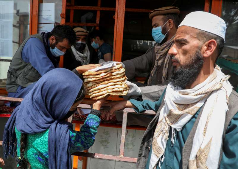 An Afghan girl receives free bread distributed by the government, outside a bakery, during the coronavirus disease (COVID-19) outbreak in Kabul