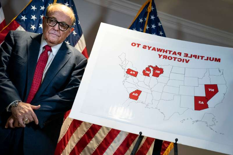 text, letter: Rudy Giuliani stands next to a map during a press conference about various lawsuits related to the 2020 election, inside the Republican National Committee headquarters on November 19, 2020 in Washington, DC.