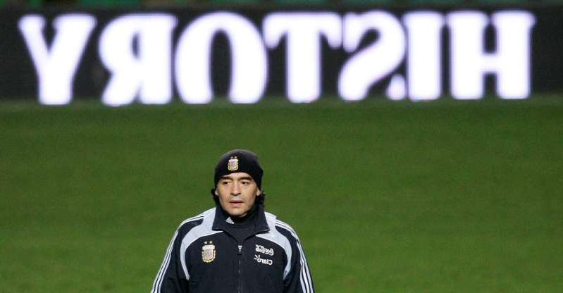 a baseball player standing on top of a grass covered field: FILE PHOTO: Maradona at Team Argentina Training in Glasgow