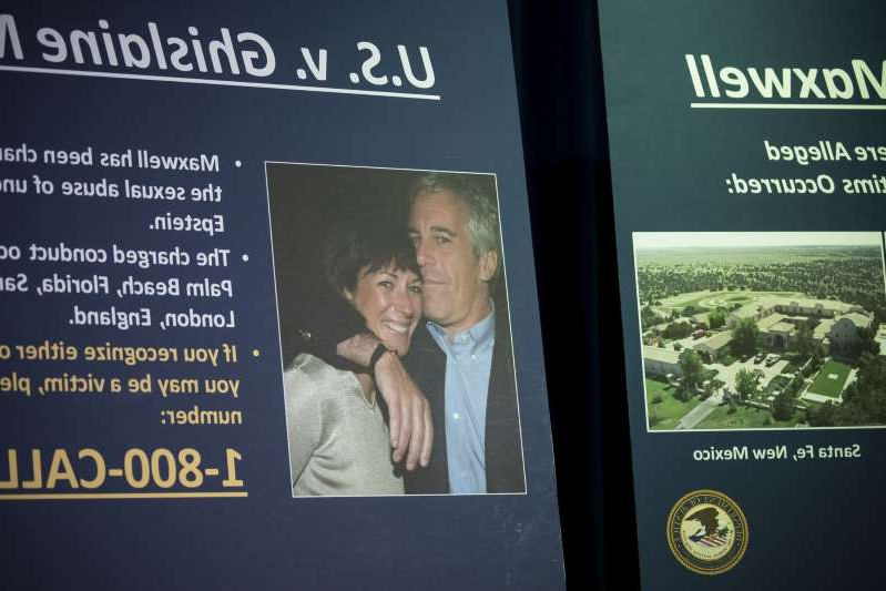 a blackboard sign next to Ghislaine Maxwell: A photograph of Ghislaine Maxwell and Jeffrey Epstein is displayed during a news conference at the U.S. Attorney's Office in New York, U.S., on Thursday, July 2, 2020.