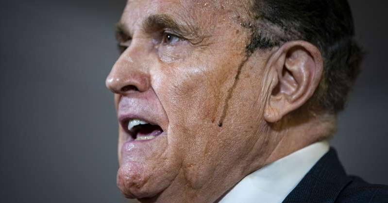 a close up of a man wearing a suit and tie: Rudy Giuliani, personal lawyer to U.S. President Donald Trump, speaks during a news conference at the Republican National Committee headquarters in Washington, D.C., on Thursday, Nov. 19, 2020.
