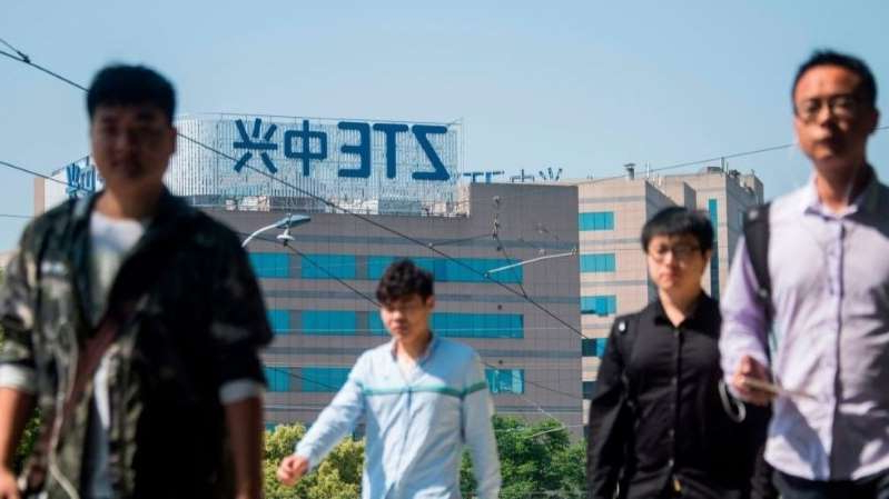 a group of people standing next to a man: FCC denies ZTE request to reverse national security threat designation