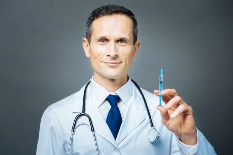 a man wearing a blue shirt: Cheerful practitioner holding syringe and smiling